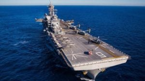 The USS America, a large air craft carrier in the ocean with several aircraft on it