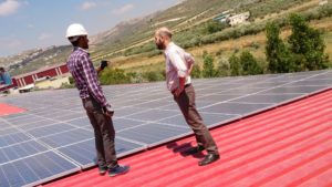 Two men stand on a roof next to many solar panels talking
