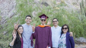 A family stands together with their ASU graduate