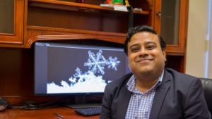 Kumar Ankit sits smiling at his desk, in front of a computer screen with snowflake images