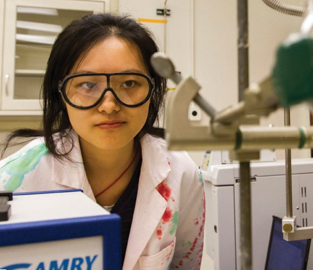 Young undergraduate woman sits in a lab in her lab coat and safety goggles looking at a piece of lab equipment