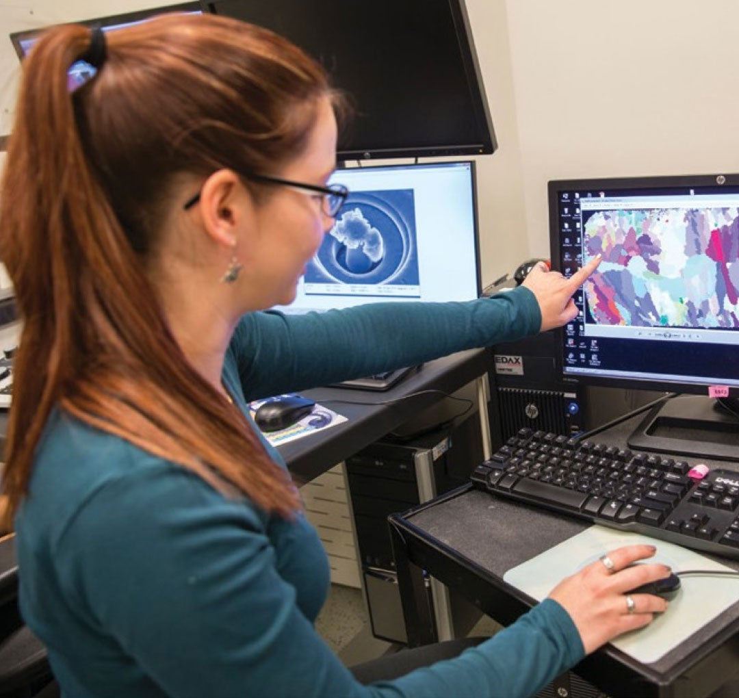 Undergraduate woman sits at a computer pointing out data on a monitor
