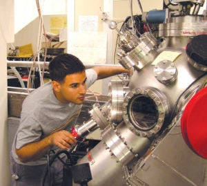 An undergraduate man looks at a large machine a lab
