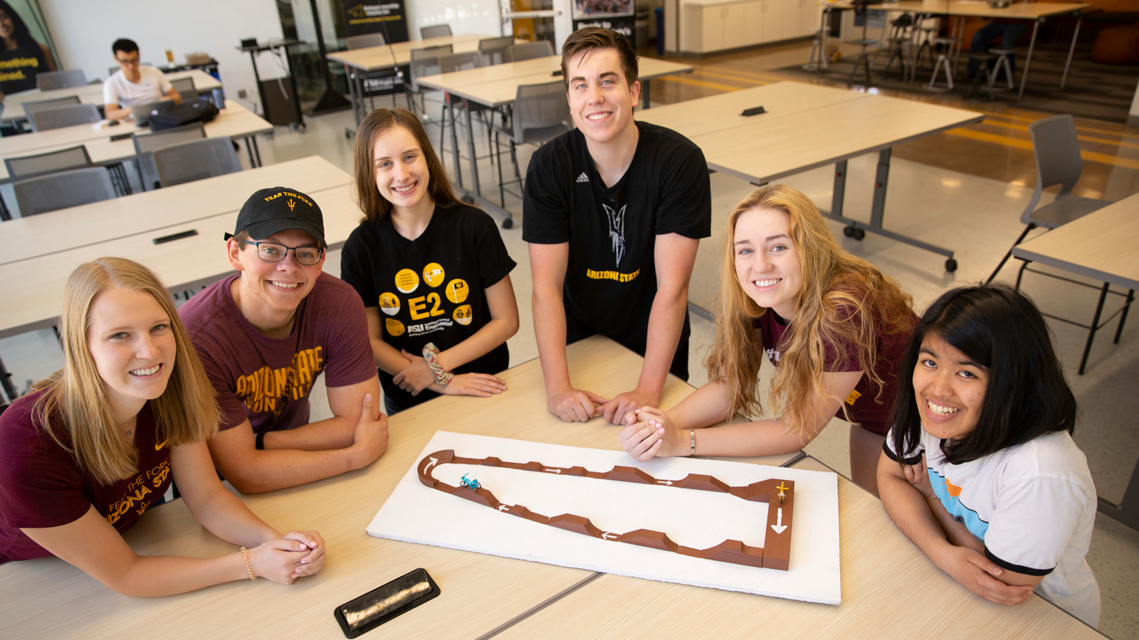 Six students on the Shonto Pump Track team assemble for a photo with their project model